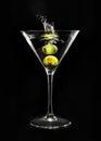 Martini glass splashing green olive in on black background Stock Images