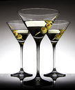 Martini glasses with olives three two on a stick on shiny black table Stock Photography