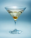 Martini with olive isolated vermouth on blue Royalty Free Stock Photos