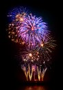 Marvelous fireworks display multi colored on black background reflected on water Royalty Free Stock Image