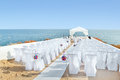 A marvelous place in the decorations and flowers for the wedding ceremony with white chairs on sea Stock Photo