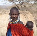 Masai mother carrying baby on back unidentified in traditional jewellery and blanket mud hut and savannah in background taken Royalty Free Stock Photography