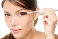 Mascara woman putting makeup on eye closeup eyes asian female model face with brush eyelashes Royalty Free Stock Image