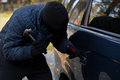 Masked burglar with hammer a trying to break in a car using a Royalty Free Stock Photos