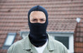 Masked burglar with roofs in the background looking at camera of homes Royalty Free Stock Photography