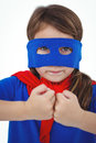 Masked girl pretending to be superhero showing fist fist on white screen Stock Photo