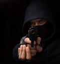 Masked robber with gun aiming into the camera Stock Photo