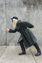 Masked woman runs to the wall current blonde in leather coat Stock Photography