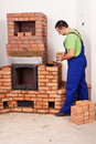 Mason building a masonry heater from red bricks and clay mortar Royalty Free Stock Photography