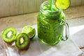 Mason jar mug with green vegetable and fruit smoothie, kiwi, lime, white wood table outdoors, sunlight fleck Royalty Free Stock Photo