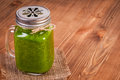 Mason jar mugs filled with green spinach and kale health smoothie swirled straw Royalty Free Stock Photo