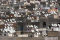 A mass of satellite discs sit atop apartment buildings in Fez in Morocco. Royalty Free Stock Photo