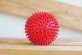 Massage ball red on wooden background Royalty Free Stock Images