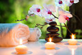Massage composition spa with candles, orchids and black stones in garden Royalty Free Stock Photo