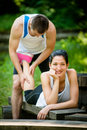 Massage after sport jogging man gives of calf to his girlfriend training women lies on bench Stock Photos