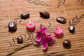 Massage stones composition on bamboo placemat candles pink flowers and in relaxation spa Stock Photography