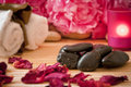 Massage stones, flowers, candles, towels. Royalty Free Stock Photo