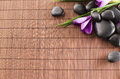 Massage stones with flowers on mat Stock Photos