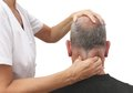 Massaging tight neck muscles female therapist working on male patient s Stock Images