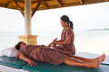 Masseuse at work on the beach in Thailand Royalty Free Stock Photo