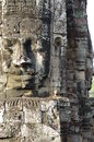 Massive stone faces of prasat bayon present on many towers in angkor thom enduring capital city the khmer empire in cambodia Royalty Free Stock Photo