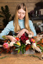 Young woman creating colorful fall bouquet at flower shop Royalty Free Stock Photo