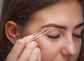 Master makeup corrects, and gives shape to pull out with forceps previously painted with henna eyebrows in a beauty salon. Royalty Free Stock Photo