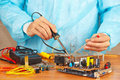 Master solder electronic components of device in service workshop the Royalty Free Stock Photo