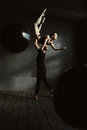 Masterful gymnasts dancing together in the black colored studio