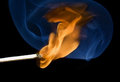 Match flame and smoke lighted blue on a black background Stock Images