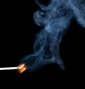 Match flame and smoke lighted blue on a black background Royalty Free Stock Photo
