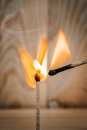 Match is ignite on a blurry wood background selective focus Stock Image