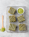 Matcha green tea brownie cake with white chocolate on a cooling rack Grey stone background Top view Copy space Royalty Free Stock Photo