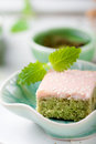 Matcha green tea cakes with white chocolate glaze and sesame seeds a cup of and balm mint leaves on a wooden Royalty Free Stock Photos