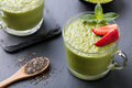 Matcha green tea chia seed pudding, dessert with fresh mint and strawberry on a black slate background Healthy breakfast Royalty Free Stock Photo