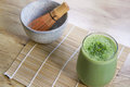 Matcha green tea smoothie with stone bowl and wooden whisk on bamboo mat on table above angle view landscape orientation Royalty Free Stock Photo