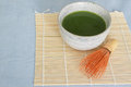 Matcha green tea in stone drinking bowl on bamboo placemat with wooden whisk front of light blue tablecloth above angle Stock Photography