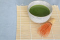 Matcha green tea in stone drinking bowl on bamboo placemat with wooden whisk front of light blue tablecloth above angle Stock Photos