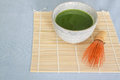 Matcha green tea in stone drinking bowl on bamboo placemat with wooden whisk front of light blue tablecloth above angle Stock Image