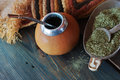 Mate calabash yerba south american tea dried leaves in wooden bowl with a wooden with tea selective focus Stock Photos