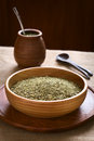 Mate tea south american yerba dried leaves in wooden bowl with a wooden cup and strainer bombilla in the back Royalty Free Stock Photo