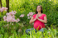 Maternity yoga peaceful meditation in field of flowers woman doing exercises while pregnant last trimester sitting a garden pink Royalty Free Stock Photo