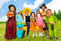 Mates in halloween costumes stand close together on green grass of the field Royalty Free Stock Photo