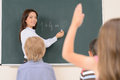 Mathematic class confident young teacher writing on the blackboard while pupils looking at her and rising their hands Stock Photo