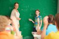 Mathematics portrait of smart teacher and schoolgirl standing by blackboard and looking at schoolkids in classroom Royalty Free Stock Images