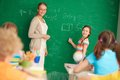 Mathematics portrait of smart teacher and schoolgirl standing by blackboard and looking at schoolkids in classroom Stock Photography
