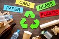 Matherials suitable for recycle near green recycle eco symbol. Words paper, glass, plastic, cans on dark wooden Royalty Free Stock Photo
