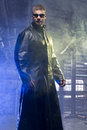 Matrix style role play character adult man in trench coat in old factory Stock Image