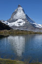 Matterhorn and reflection the in the southern swiss alps close to zermatt with cloud around its base a in a lake in the foreground Royalty Free Stock Images