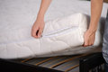 Mattress demonstration of quality a young man holding demonstrations quality in the bedroom Royalty Free Stock Image